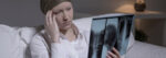 Despairing woman with brain cancer looking at x-ray photo